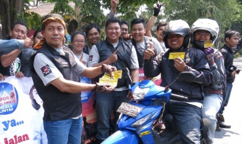 Anggota klub Honda Vario membagikan stiker bertema kampanye keselamatan berkendara kepada pengendara sepeda motor yang melintas di jalan Slamet Riyadi dalam rangkaian acara Jambore Nasional Paguyuban Vario Nusantara kelime di Solo (27/9). Pada ajang tersebut, 900 lebih anggota komunitas dan pecinta sepeda motor Honda Vario se-Indonesia melakukan kampanye keselamatan berkendara serta aksi kepedulian sosial kepada anak yatim piatu.