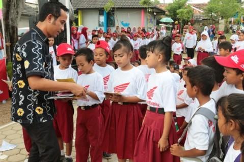 Deputy Head of Corporate Communication AHM Ahmad Muhibbuddin membagikan buku kepada siswa siswi SD di Kalihurip. AHM bersama komunitas Sahabat Satu Hati secara serentak membagikan sekitar 5.000 buku di SD Negeri Kalihurip 1, SD Negeri Kalihurip 2, dan SMA Negeri 2 Cikampek sebagai upaya mencerdaskan generasi muda melalui kampanye gemar membaca buku